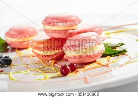Macarons in white plate. French dessert. Sandwich cookies with buttercream filling. Delicious biscuits with cream and pink food coloring side view. Sweet confection, bakery
