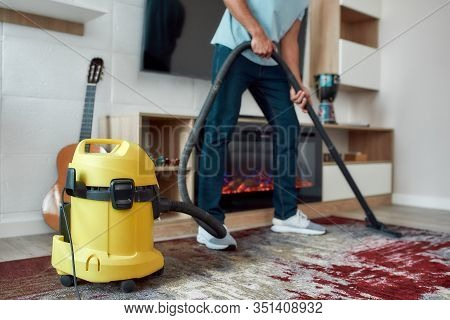 Cropped View Of Young Man Cleaning The Carpet With Vacuum Cleaner While Working In The Modern Living