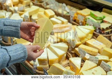 Man Shopping Cheese In Grocery Store. Cheese In Hands Of Buyer On Background Of A Large Selection Of