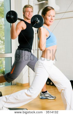 poster of Very attractive and sportive couple doing power gymnastics with barbells