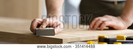Carpenter Man Grinds Wooden Sheet In Workshop. Workplace Joiner Is Equipped With Workbench On Which