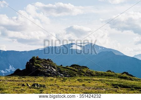 Awesome Alpine Landscape With Beautiful Rock On Green Mountain Peak In Background Of Great Snowy Mou