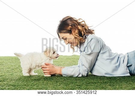 Side View Of Smiling Woman Looking At Havanese Puppy Isolated On White