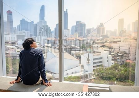 Young Asian Business Man Sitting On Bench In Office Building Looking Through The Glass Window With C