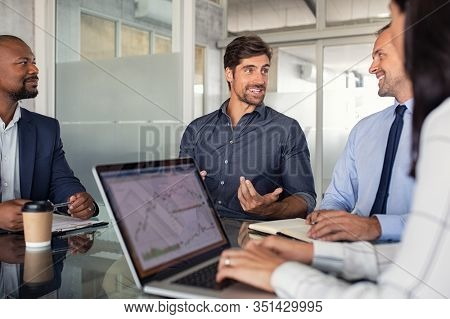Group of business people discussing financial matter during meeting. Team of business partners at work in office. Businessmen and businesswoman sitting at conference table and working together.