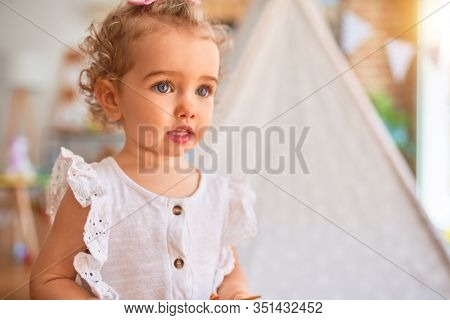 Beautiful caucasian infant playing with toys at colorful playroom. Happy and playful at kindergarten.