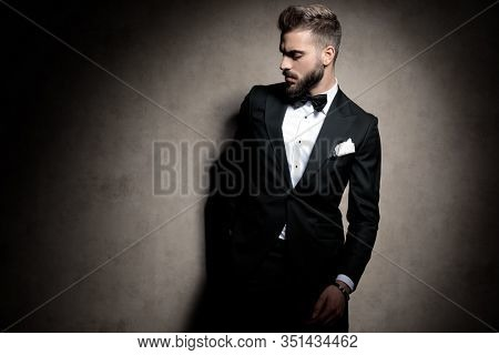 elegant fashion man in tuxedo holding hands in pockets and looking down, posing in a fashion light on brown background in studio