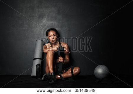 Image of young african american sportswoman wearing hand wraps sitting on floor with fitness equipment isolated over black background