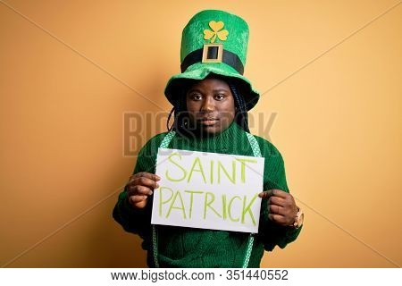 Plus size african american woman wearing green hat holding banner on saint patricks day with a confident expression on smart face thinking serious