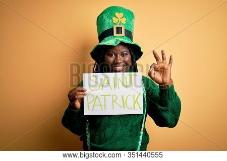 Plus size african american woman wearing green hat holding banner on saint patricks day doing ok sign with fingers, excellent symbol