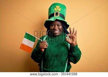 Plus size african american woman wearing green hat holding irish flag on saint patricks day doing ok sign with fingers, excellent symbol