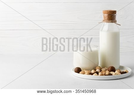 Dairy-free Milk. Macadamia Nut Milk In A Glass Cup And A Bottle On A White Background. Dairy Product