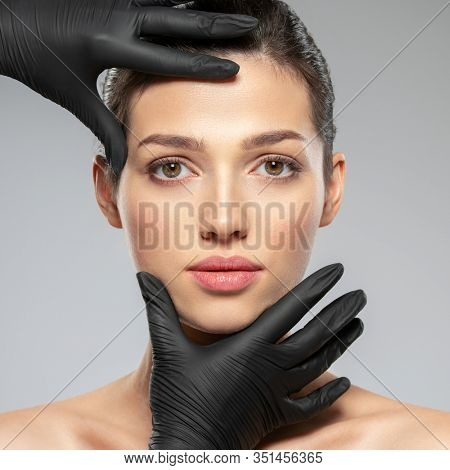 Doctor checks a skin before plastic surgery.  Face skin check before plastic surgery. Beautician touching woman face.Beauty treatments. Plastic surgery doctor is touching face of a patient by hands