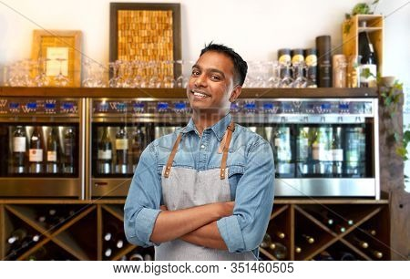 people, job and profession concept - smiling indian barman, waiter or salesman in apron over wine bar background