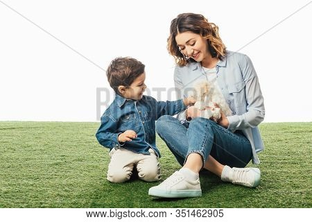 Smiling Mother Holding Havanese Puppy And Son Stroking It Isolated On White
