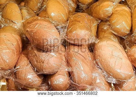 A Lot Of Loaves Of Wheat Bread In The Package On The Counter In The Store. Abstract Background Of Lo