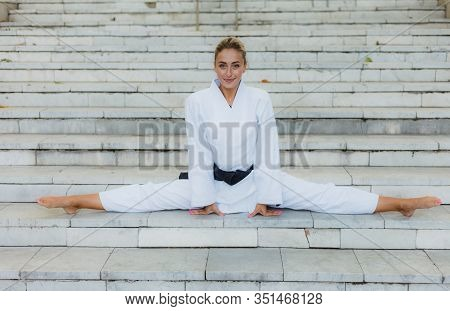 Young Attractive Woman In White Kimono With Black Belt. Sport Woman Sitting In Twine On Stairs Outdo