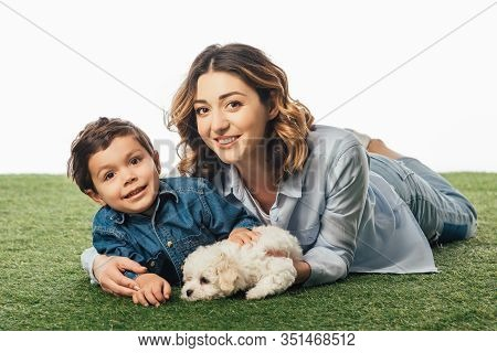 Smiling Mother And Son Lying On Grass With Havanese Puppy Isolated On White