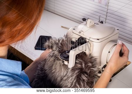 Professional Master In The Manufacture Of Clothing From Fur. Woman Couturier At The Sewing Machine.