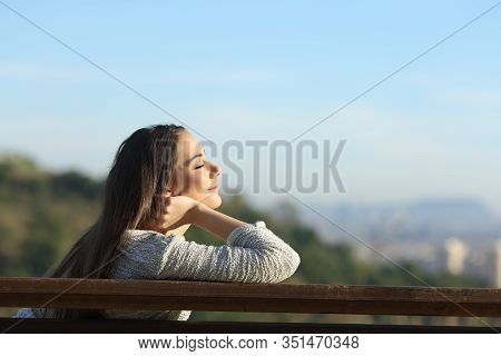 Side View Portrait Of Woman Relaxing Relieving Stress Sitting On A Bench In City Outskirts