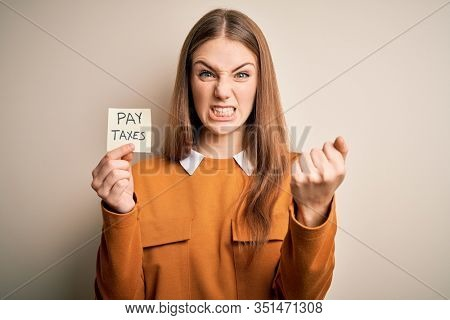 Young beautiful blonde woman holding pay taxes to goverment reminder over yellow background annoyed and frustrated shouting with anger, crazy and yelling with raised hand, anger concept