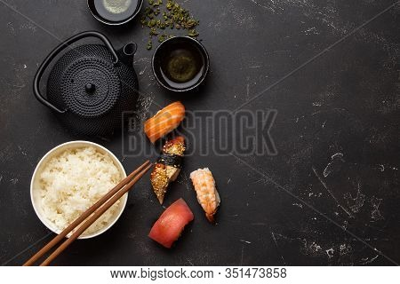 Set Of Traditional Japanese Food: Boiled White Rice, Sushi, Fish Rolls, Green Tea In Teapot On Black