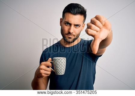 Young handsome man drinking a cup of hot coffee over white isolated background with angry face, negative sign showing dislike with thumbs down, rejection concept