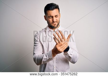 Young handsome man wearing elegant shirt standing over isolated white background Suffering pain on hands and fingers, arthritis inflammation