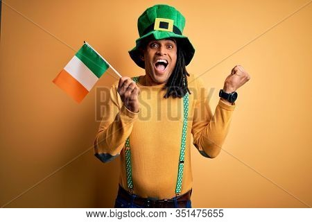 African american man wearing green hat holding irish ireland flag celebrating saint patricks day screaming proud and celebrating victory and success very excited, cheering emotion