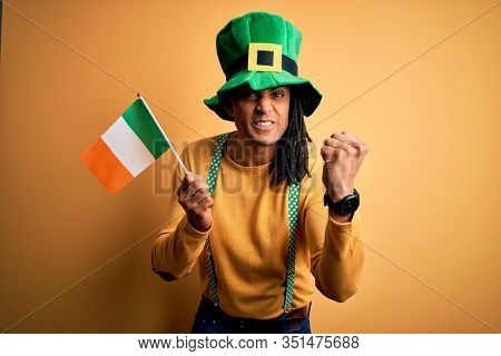 African american man wearing green hat holding irish ireland flag celebrating saint patricks day annoyed and frustrated shouting with anger, crazy and yelling with raised hand, anger concept