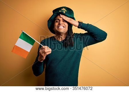 African american man wearing green hat holding irish ireland flag celebrating saint patricks day stressed with hand on head, shocked with shame and surprise face, angry and frustrated. Fear and upset