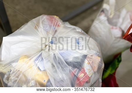 Close-up Tied Full Household Plastic Waste Bag Filled With Non-recyclable Rubbish At Recycling Accep