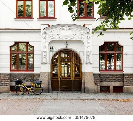 Malmo Sweden August 10, 2017: A Postman Bike Parked Outside A Posh Entrance To An Old White Building