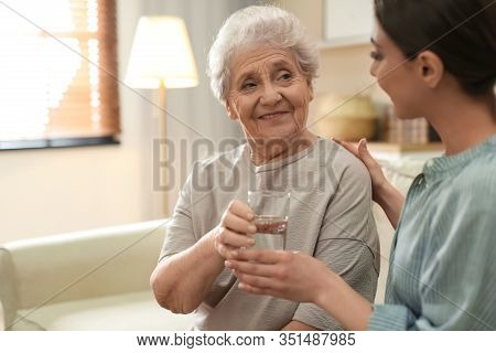 Young Woman Giving Water To Elderly Lady Indoors. Senior People Care