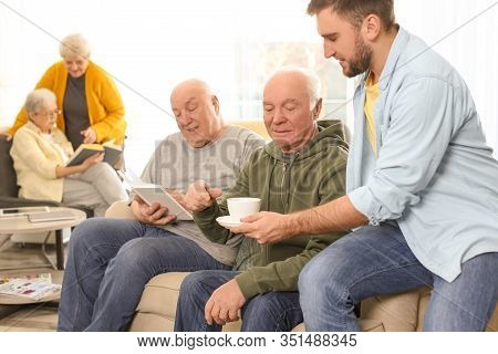 Young Man Taking Care Of Elderly People In Geriatric Hospice