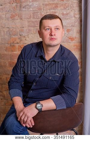 A Man Against A Brick Wall Background. Man On A Brick Background. Portrait Of A Man 30 Or 35 Years O