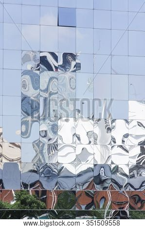 Detail Of Reflective Glazed Building In Which The Surrounding Constructions Are Reflected, Deformed.