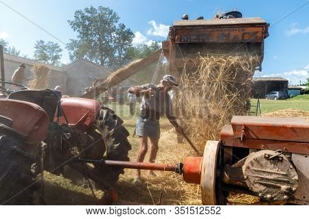 GENSAC, FRANCE, JULY 28, 2019 : French farmers working with a restored ancient threshing machine for wheat, built in 1922