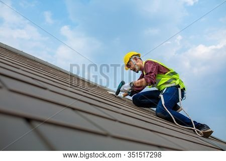 Construction Workers Fixing Roof Tiles, With Roofing Tools, Electric Drills Used On Roofs In Safety