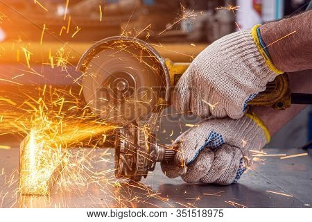 Close-up On The Sides Fly Bright Sparks From The Angle Grinder Machine. A Young Male Welder  Grinds