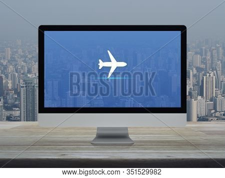 Airplane Flat Icon On Desktop Modern Computer Monitor Screen On Wooden Table Over Office Building To