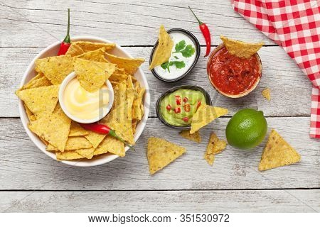 Mexican nachos chips with various sauces - guacamole, salsa, cheese and sour cream. Top view flat lay on wooden table