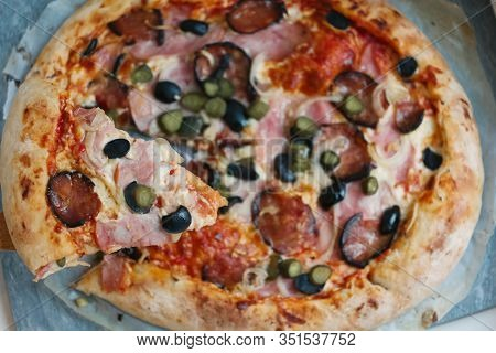 Slice Of Pizza With Hum, Sausage,cucumber, Olives Onion And Cheese Crust