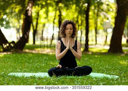Woman Practices Yoga In Morning In Park In Fresh Air. Lotus Pose.