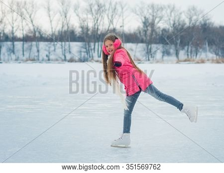Girl Teenager Skating With White Skates On The Ice Area In Winter Day. Young Figure Skating Girl At