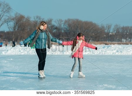 Smiling Young Mother And Her Cute Daughter Ice Skating Together By Hands. Family Skating And Trainin