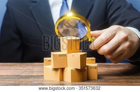 Businessman Examines Boxes Goods With Magnifying Glass. Marketing Sales Promotion Strategy. Trade Ma