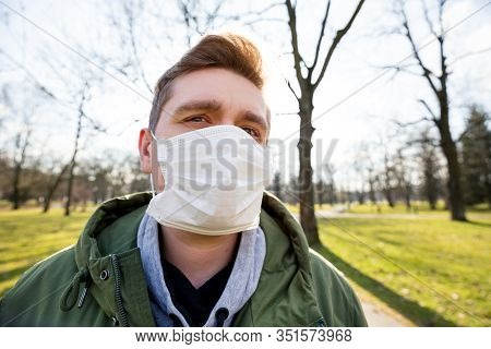 Portrait Of A Man Wearing Medical Mask On A City Public Park Bacground. Corona Virus Pandemic. Conce