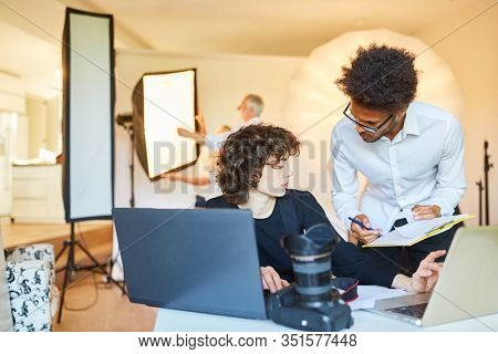 Photographer and photo assistant with clipboard at postproduction in the studio