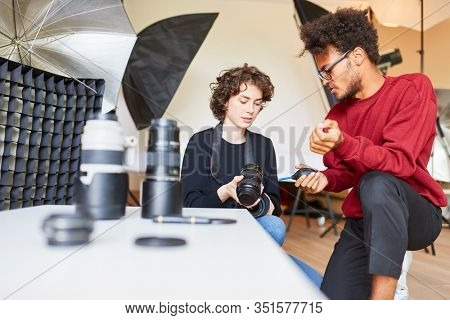 Photographer and photo assistant with lens cleaning with bellows